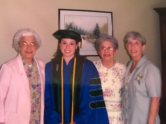 Dr. Malone (center) graduating from Medical School