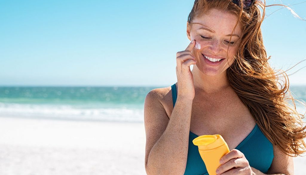 woman holding suncreen on beach