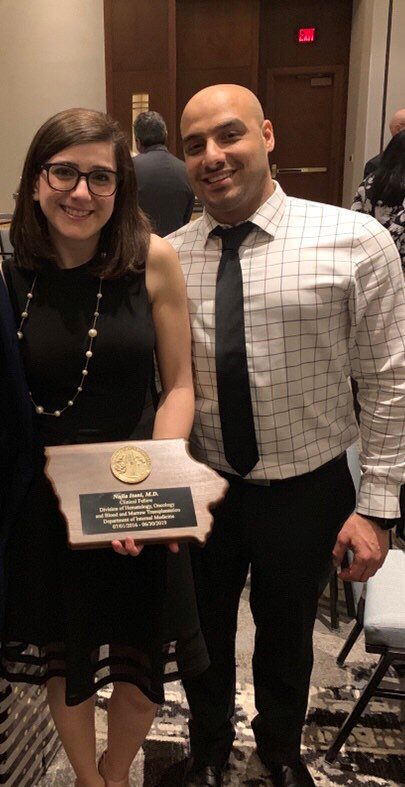 Dr. Najla Itani holding an award with her husband.