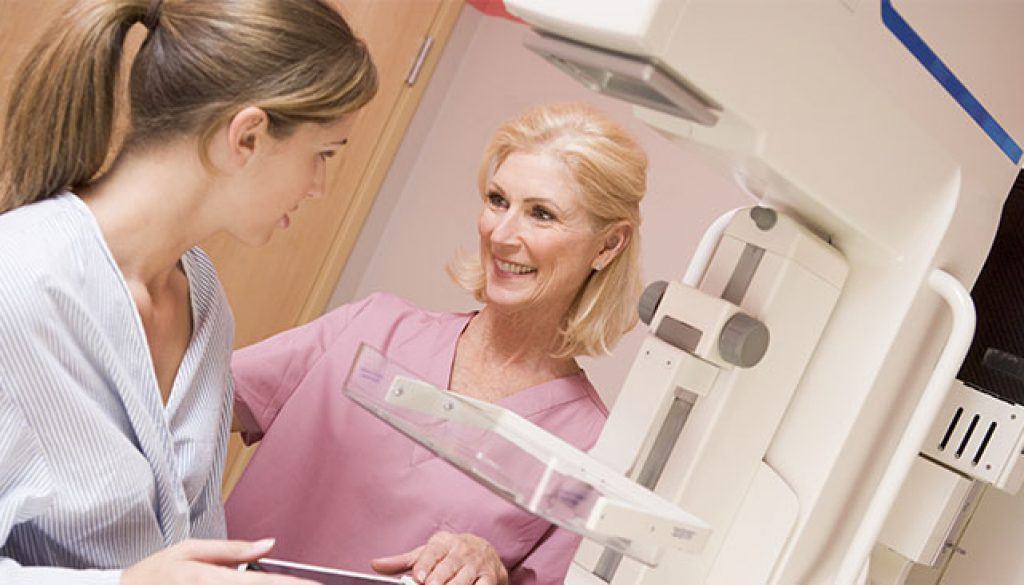 Smiling nurse helps woman receive a 3D Mammogram, available in Conway, SC.