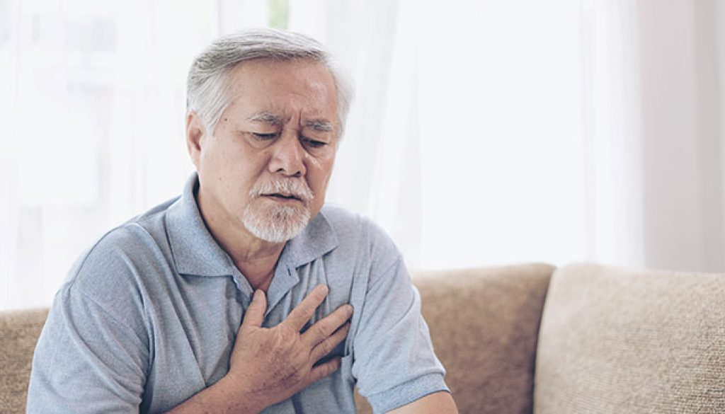 Senior Asian male holding chest because of heart burn.