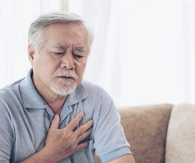 Senior Asian male holding chest because of heart burn.