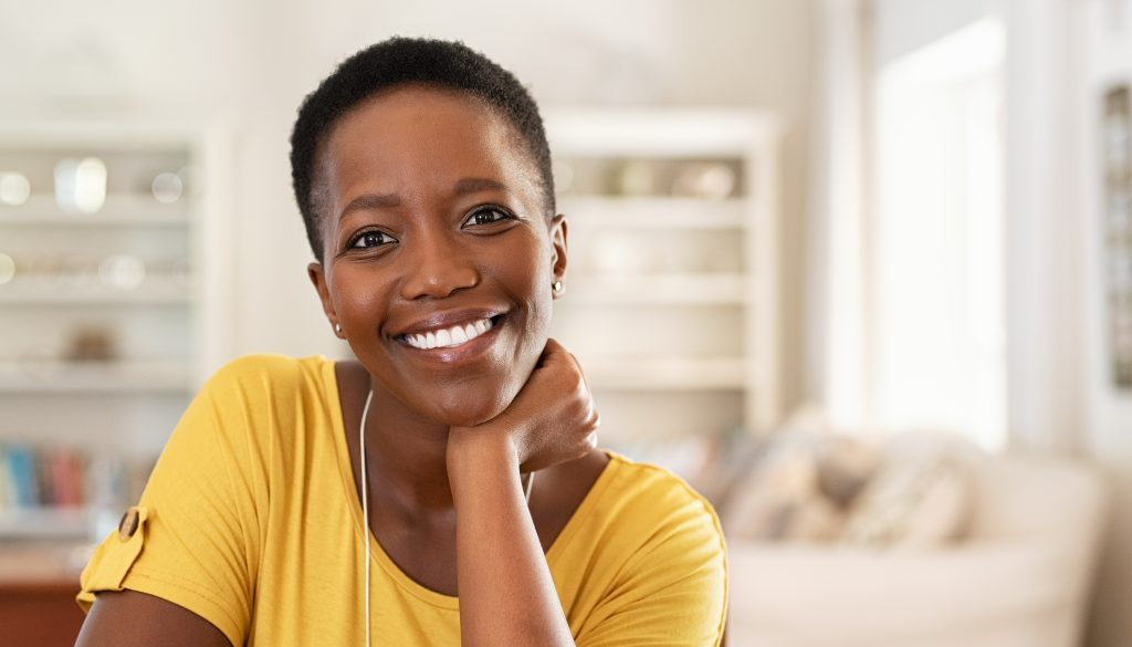 Portrait of mature woman sitting at home and looking at camera.