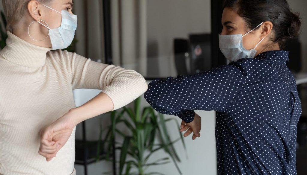Healthy diverse colleagues in facial masks bumping elbows.