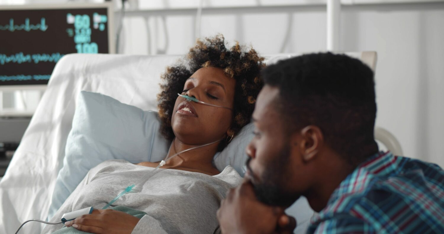 Worried african husband sitting at sick wife bed in hospital