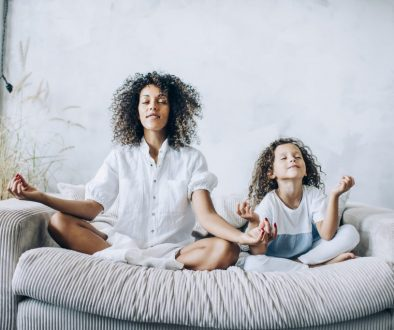 Cute girl and mother meditating on couch